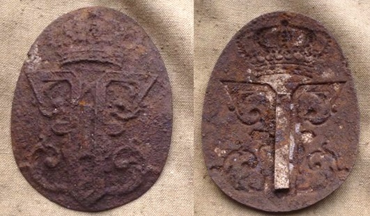An emblem with a Ferdinand I monogram found during diggings.